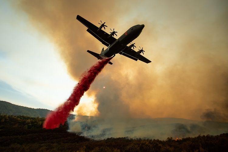 Sebuah pesawat tanker menyiramkan air ke arah lokasi kebakaran hutan di California, AS.