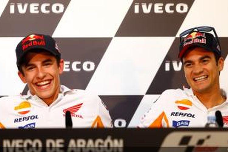 Dua pebalap Honda, Marc Marquez (kiri) dan Dani Pedrosa, tersenyum saat menghadiri konferensi pers jelang GP Aragon, Kamis (26/9/2013).