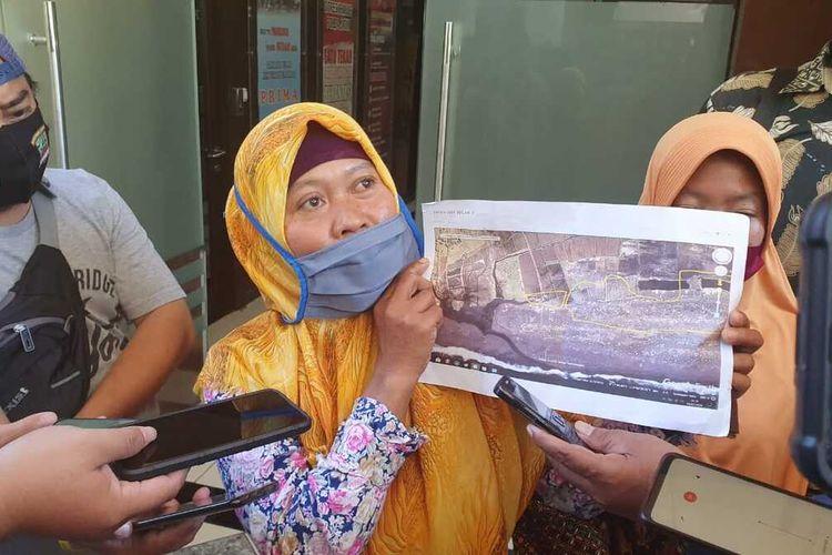 Tijah, isteri aktivis Salim Kancil menunjukkan peta lokasi tanahnya yang diduga diserobot perusahaan pengelola tambak udang, Rabu (12/8/2020) di Mapolda Jatim.