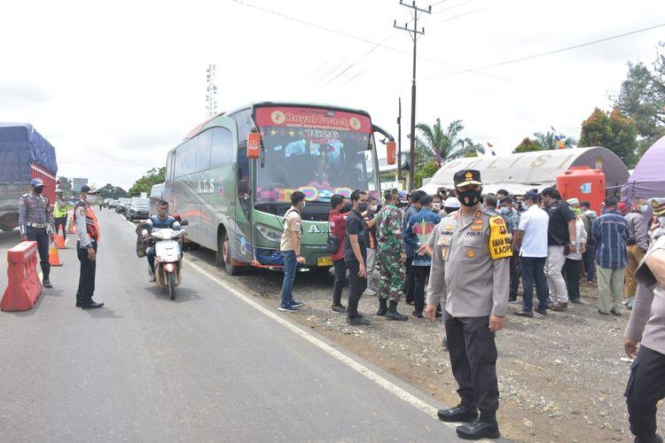 Pihak kepolisian saat memberhentikan bus untuk menegakkan aturan larangan mudik di daerah perbatasan Jambi-Sumatera Selatan