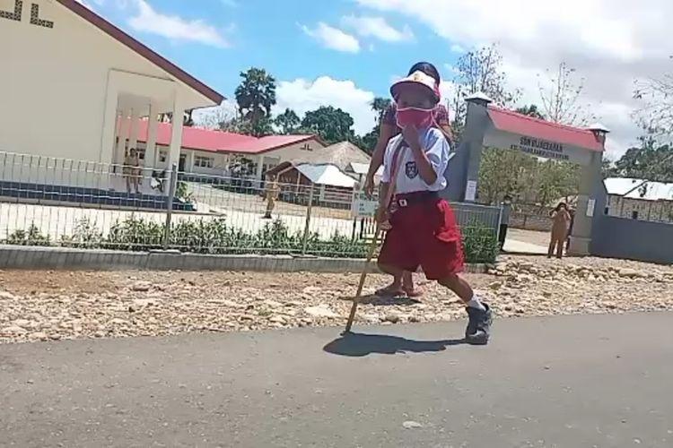 Stenly Yesi Ndun, bocah berusia tujuh tahun yang memiliki satu kaki, saat memakai tongkat untuk ke sekolah