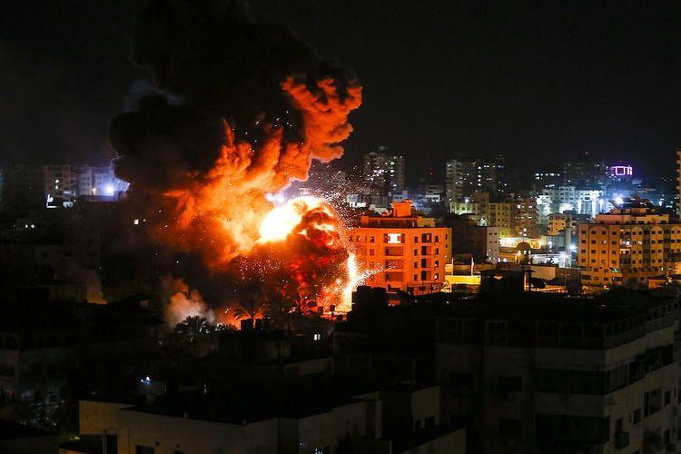 Asap disertai pijaran api membubung dari salah satu gedung di Gaza ketika jet tempur Israel menyerang sebagai bentuk balasan setelah roket menghantam Tel Aviv pada Senin (25/3/2019).