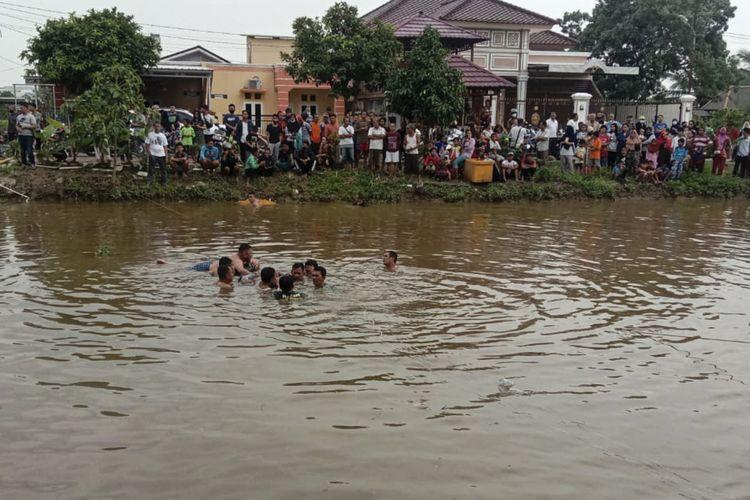 Warga saat melakukan evakuasi terhadap Atik Fitriati (53) pengemudi mobil yang nyemplung ke sungai kawasan Dekranasda Jakabaring akibat hilang kendali. Atik diketahui saat itu sedang belajar menyetir bersama suaminya yang berhasil selamat.
