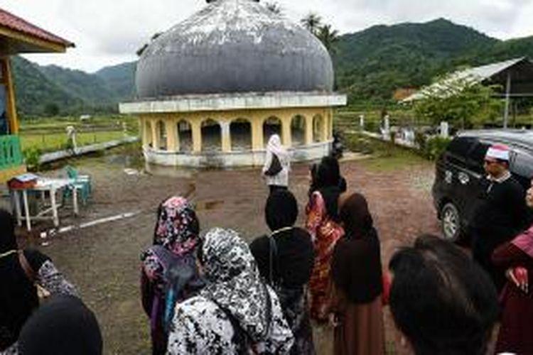 Wisatawan dari perkumpulan pengajian Masjid Tengku Ampuan Jamaah, Syah Alam, Selangor, Malaysia mengunjungi situs tsunami kubah masjid yang hanyut di Desa Gurah, Kecamatan Peukan Bada, Aceh Besar, Minggu (26/10/2014). Saat musibah tsunami melanda Aceh 26 Desember 2004 lalu, kubah masjid tersebut terseret arus sekitar 2,5 kilometer dari posisi sebelumnya di Desa Lam Teungoh, Aceh Besar.