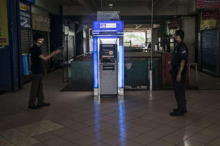 Petugas kebersihan menyemprotkan cairan disinfektan di sebuah mesin ATM di Pasar Palmerah, Jakarta, Jumat (26/6/2020). Pengelola Pasar Palmerah menutup sementara pasar tersebut dari Kamis (25/6) hingga Sabtu (27/6) menyusul sembilan orang pedagang terkonfirmasi positif COVID-19 dalam tes usap yang dilakukan sebelumnya.