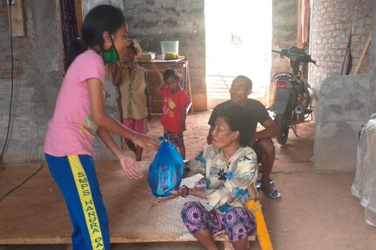 Foto : Julian Intan Lestari Sada Beli (14), seorang siswi Kelas IX SMPK Hanura Danga, Kecamatan Aesesa, Kabupaten Nagekeo, memberikan sembako kepada keluarga yang membutuhkan, Kamis.