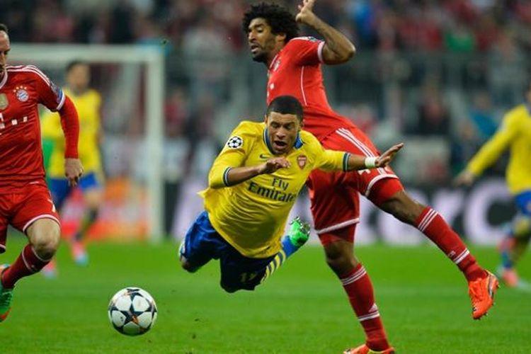 Gelandang Arsenal, Alex Oxlade-Chamberlain, terjatuh dalam pertandingan leg kedua babak 16 besar Liga Champions melawan Bayern Muenchen di Allianz Arena, Selasa (11/3/2014).