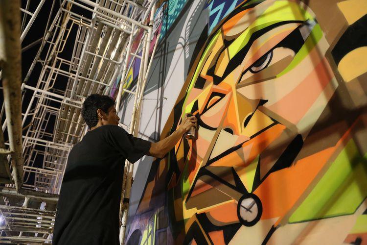 Seniman graffiti (bomber) sedang mengerjakan mural dengan tema Kalijodo dan sejarahnya di Ruang Publik Terpadu Ramah Anak (RPTRA) Kalijodo, Jakarta, Rabu (8/2/2017). Pengerjaan grafiti dan mural yang dilakukan ArtSip Jakarta 2017 dimulai pada Minggu (5/2/2017) sore dan melibatkan 11 seniman grafiti atau bomber.