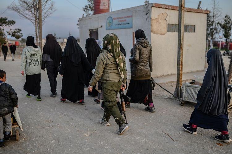 Para perempuan yang dikabarkana dalah para istri anggota ISIS berjalan di bawah pengawasan anggota perempuan Tentara Demokratik Suriah (SDF) di kamp al-Hol, provons Hasakeh, Suriah.