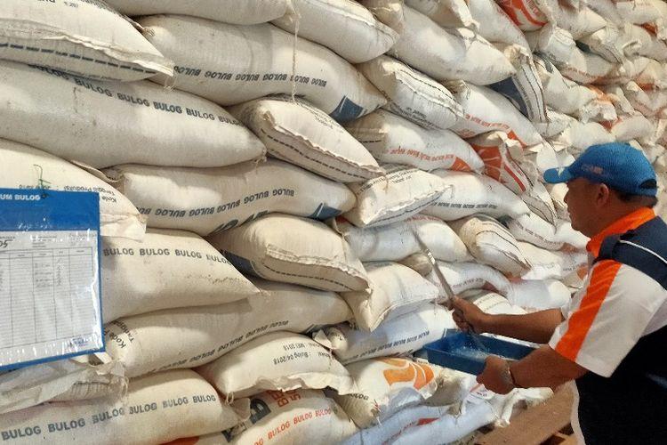 Seorang pegawai mengecek kualitas beras yang tersimpan di Gudang Bulog Munjung Agung, Kabupaten Tegal, 23 Maret 2021.