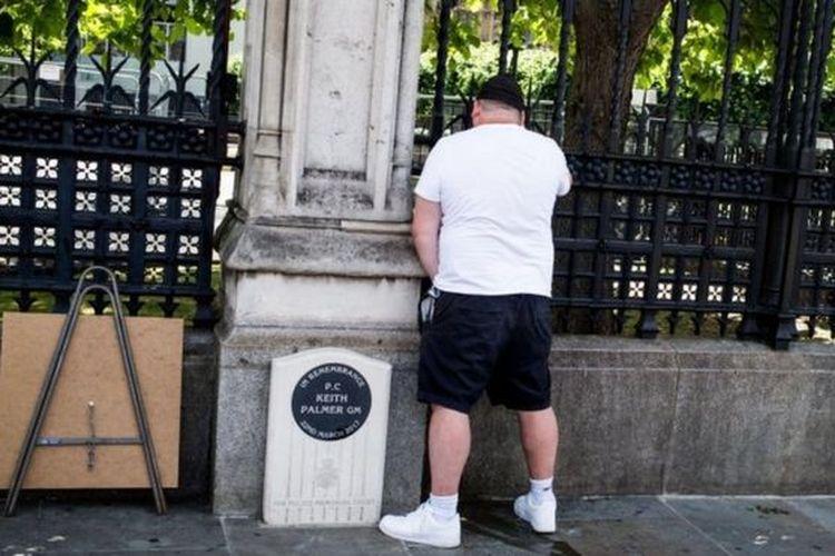 Seorang pria tampak mengencingi batu peringatan atas kematian PC Keith Palmer di Westminster, London, Inggris.