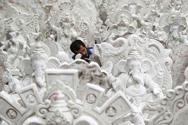 Seorang pria membuat patung dewa Hindu Ganesha, dewa kemakmuran, sebelum festival Chaturthi Ganesha di Mumbai, India, Minggu (19/7/2020).