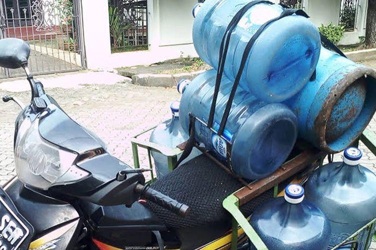 Sepeda motor angkut galon air minum dan tabung gas elpiji.