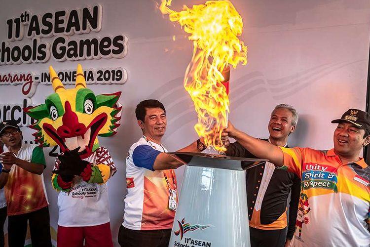 Gubernur Jateng Ganjar Pranowo (tengah) bersama Wali Kota Semarang Hendrar Prihadi (kanan) dan Asisten Deputi Pembibitan Iptek dan Olahraga Kemenpora Wasinton (kiri) menyalakan api kaldron dalam rangkaian estafet obor api ASEAN School Games (ASG) XI 2019 di Semarang, Jawa Tengah, Rabu (17/7/2019). Api yang diambil dari Api Abadi Mrapen, Grobogan itu selanjutnya akan digunakan dalam prosesi pembukaan ASG XI 2019 pada Kamis (18/7/2019) besok di Holy Terang Bangsa School, Semarang.