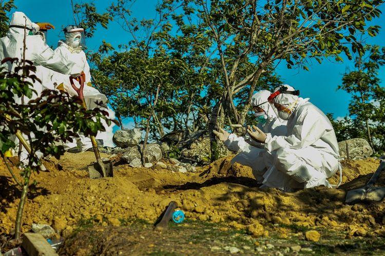 Sejumlah petugas mendoakan seorang Pasien Dalam Pengawasan (PDP) COVID-19 yang baru saja dimakamkan di Tempat Pemakaman Umum (TPU) Poboya, Palu, Sulawesi Tengah, Senin (11/5/2020). PDP berusia 56 tahun itu meninggal dunia dalam perawatan di Rumah Sakit Undata Palu. Data Gugus Tugas COVID-19 Sulteng per 11 Mei 2020, jumlah kasus positif COVID-19 sebanyak 83 orang, PDP 31 orang, 3 meninggal dunia, dan 13 orang dinyatakan sembuh. ANTARAFOTO/Eddy Djunaedi/bmz/hp.