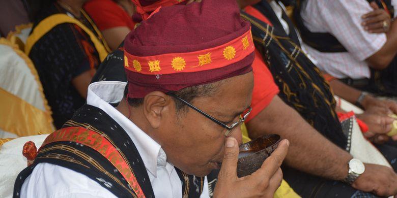 Seorang tua adat Kampung Langa sedang minum tuak atau mokel lokal pengganti minuman air setelah makan uwi (ubi) saat ritual Reba Ngada dilangsungkan di Kampung Langa, Kecamatan Bajawa, Kabupaten Ngada, Flores, NTT, Selasa (15/1/2019).