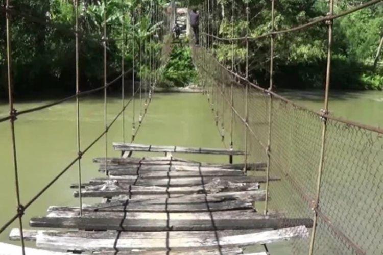 Warga Desa Pamoseang, Kecamatan Mambi, Kabupaten Mamasa, Sulawesi Barat, terpaksa bergelantungan di tali jembatan yang rusak.