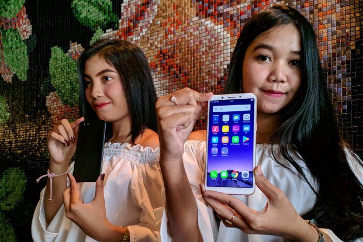 Model memamerkan smartphone Oppo A83 yang memiliki layar kekinian rasio 18:9 dan fitur face unlock di Jakarta, Rabu (21/2/2018).