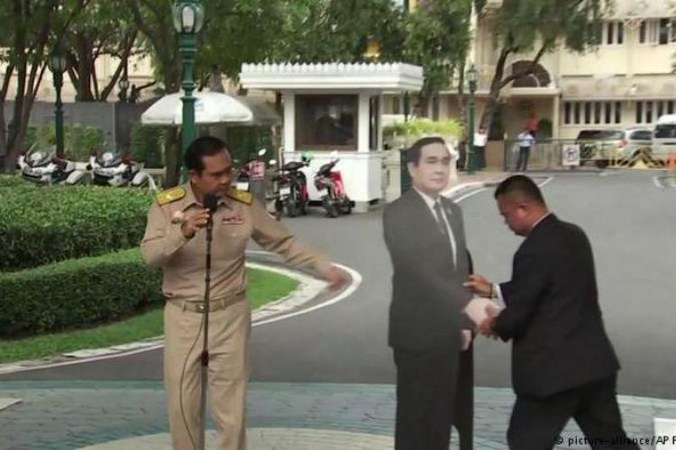 Perdana Menteri Thailand, Prayuth Chan-o-cha, memasang papan bergambar dirinya ketika konferensi pers berlangsung Senin (8/1/2018).