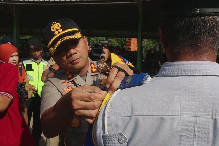 Kapolres Cirebon, AKBP Suhermanto memasangkan pita di pundak salah satu personel dalam apel operasi ketupat 2019 di Gor Ranggajati Cirebon, Selasa (28/5/2019).