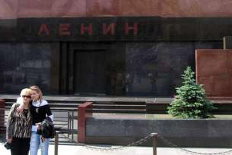 Dua wisatawan sedang berpose di depan pintu masuk mausoleum tempat jasad Tokoh Komunis Rusia Vladimir Lenin disemayamkan. Pada hari-hari tertentu, tempat ini dibuka untuk umum, dan pengunjung dapat melihat jenazah Lenin yang diletakkan dalam peti kaca.