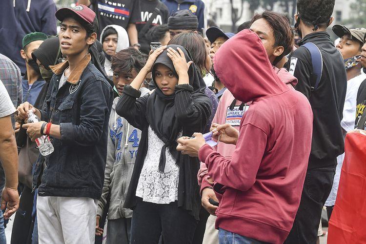 Anak di bawah umur mengikuti aksi tolak UU Cipta Kerja di kawasan Patung Kuda, Jakarta, Selasa (13/10/2020). Aksi menolak UU Cipta Kerja yang awalnya hanya banyak digelar kaum buruh dalam perkembangannya juga diikuti berbagai elemen masyarakat, dari mahasiswa, pelajar, hingga anak-anak di bawah umur.