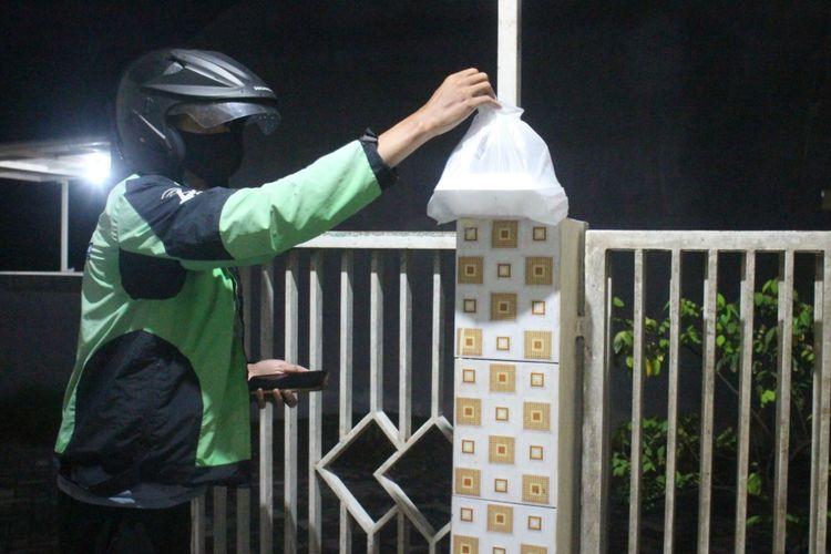 Salah seorang Driver Ojol Gojek di Kabupaten Jember gojek  mengantarkan makanan pada customer