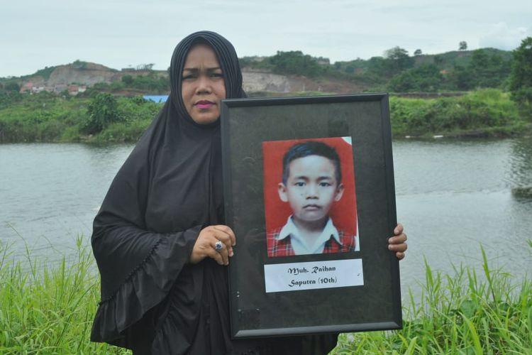 Rahmawati memegang foto anaknya Muhammad Rehan Saputra (10) di lokasi bekas lubang tambang batu bara, tempat meninggal Rehan. Beralamat di Gang Saliki, Jalan Padat Karya, Kelurahan Sempaja Selatan, Kota Samarinda, Kalimantan Timur, 2015.