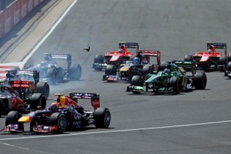 Puing-puing bertembaran saat sejumlah mobil Formula 1 berusaha melewati tikungan pertama pada balapan GP Inggris di Sirkuit Silverstone, Minggu (30/6/2013).