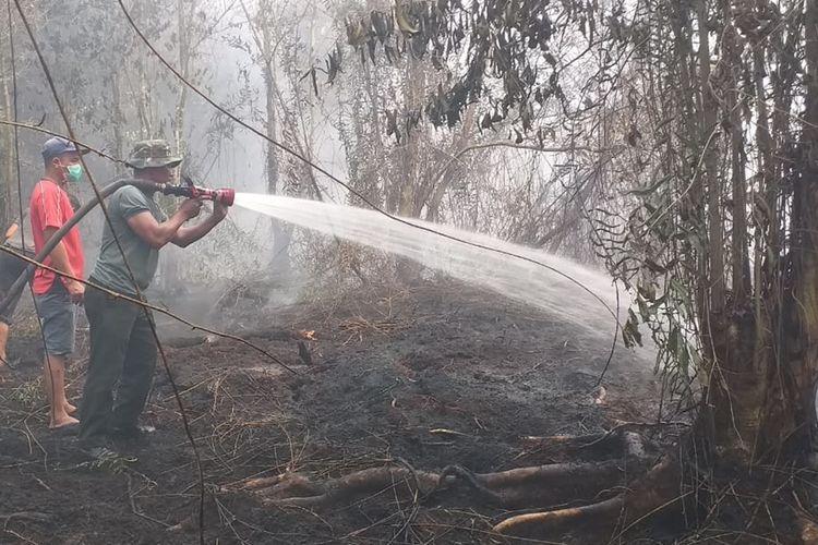 Petugas TNI dan warga memadamkan api karhutla yang mendekati rumah warga di Desa Rimbi Panjang, Kecamatan Tambang, Kabupaten Kampar, Riau, Selasa (17/9/2019)