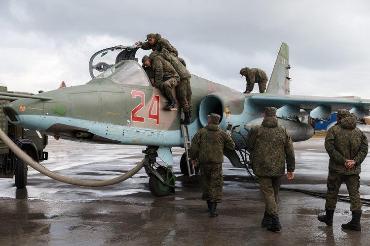 Dalam foto yang diambil pada 16 Maret 2016 terlihat para personel militer Rusia memeriksa sebuah jet tempur Sukhoi Su-25 sebelum lepas landas dari Pangkalan AU Khmeimim di Latakia, Suriah.