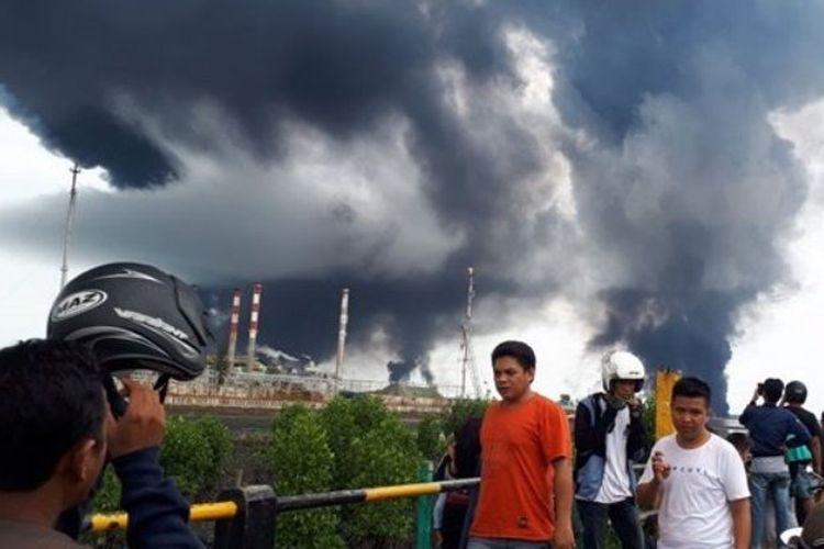 Warga melihat asap tebal yang menyelimuti Kota Balikpapan, Sabtu (31/3/2018)