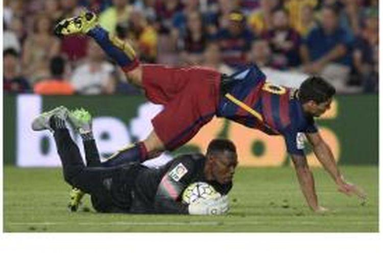 Penyerang Barcelona Luis Suarez (kiri) berjibaku dengan kiper Malaga asal Kamerun Carlos Idriss Kameni pada pertandingan La Liga di Camp Nou, Sabtu (29/8/2015). Barca menang 1-0.