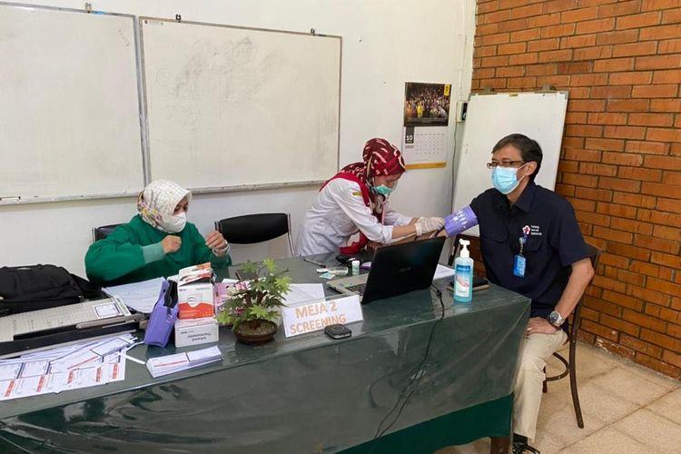 Tenaga kesehatan lanjut usia, Suhara Manulang (61) menjalani vaksinasi Covid-19 di Puskesmas Serpong Satu, Tangerang Selatan, Rabu (10/2/2021).