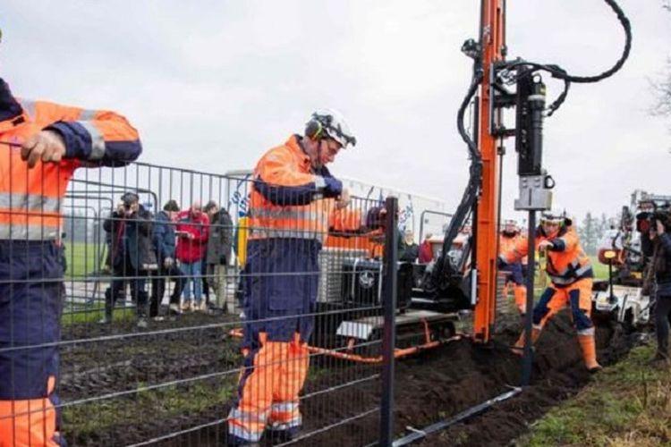 Para pekerja Denmark ketika mengerjakan pagar di perbatasan Jerman untuk menangkal migrasi babi hutan luar demi mencegah penyakit demam babi Afrika.