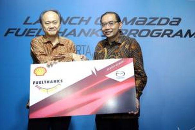 Keizo Okue, President Director Mazda Motor Indonesia (kiri) dan Wahyu Indrawanto, General Manager Retail for Shell Indonesia, Singapore, and Hongkong, memegang simbol Mazda Fuelthanks sebagai tanda peluncuran di Jakarta, Selasa (7/7/2015).