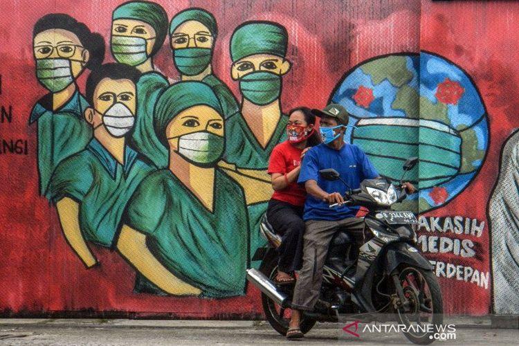 Pengendara motor melintas di depan mural tentang pandemi virus corona atau COVID-19 di Jalan Raya Jakarta-Bogor, Depok, Jawa Barat, Jumar (3/4/2020). Mural tersebut ditujukan sebagai bentuk dukungan kepada tenaga medis yang menjadi garda terdepan dalam menghadapi COVID-19 di Indonesia.