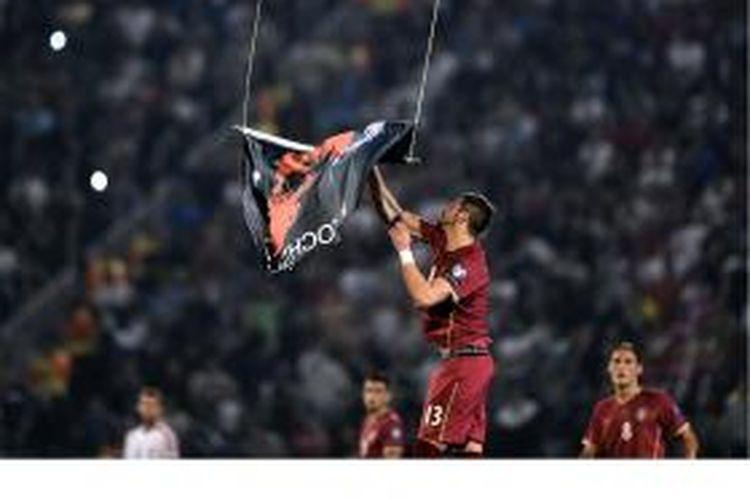 Pemain belakang Serbia, Stefan Mitrovic, menangkan dan menurunkan bendera dengan simbol Albania, yang sebelumnya diterbangkan menggunakan drone saat laga kualifikasi Grup I Piala Eropa 2016 antara Serbia dan Albania di Belgrade.