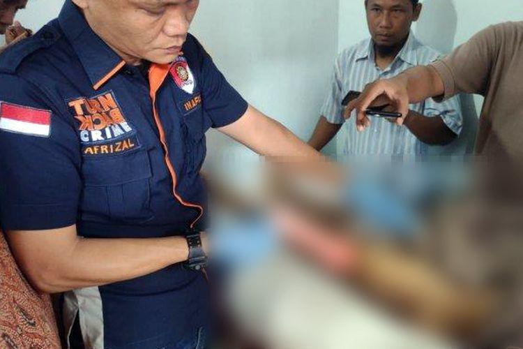 Petugas kepolisian melakuan identifikasi jenazah Aga Trias Tahta, mahasiswa Fisip Unila yang meninggal saat mengikuti diksar UKM pecinta alam Cakrawala. Kepolisian menemukan luka lebam di tubuh jenazah. (Foto: Humas Polda Lampung)