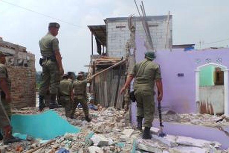 Petugas Satpol PP Bongkar bangunan warga Ria Rio yang telah pindah di rusun Pinus Elok, Cakung, Jakarta Timur. Sabtu (26/10/2013).