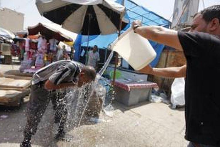 Seorang pria mendinginkan badannya dari terjangan udara panas di Baghdad dengan membasahi diri menggunakan seember air. Gelombang udara panas tengah menerjang wilayah Timur Tengah dengan di beberapa wilayah suhu mencapai di atas 70 derajat Celcius.