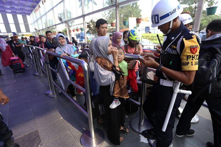 Seorang petugas memeriksa tiket pemudik di Stasiun Pasar Senen, Jakarta, Minggu (10/6/2018). Puncak arus mudik di Stasiun Pasar Senen diperkirakan jatuh pada 13 Juni 2018 atau H-2 Idul Fitri.