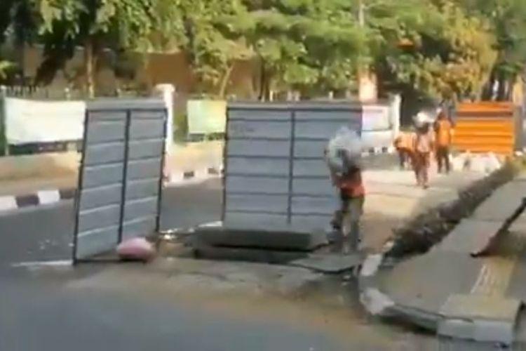 Potongan gambar dari video kegiatan pekerja memasukkan karung pasir ke lubang galian di jalan
