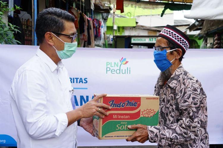 General Manager PLN Unit Induk Distribusi Jakarta Raya, M. Ikhsan Asaad (Kiri, Baju putih) menyerahkan bantuan berupa Sembako kepada  Warga RT 12 RW 16 Jl Tenaga Listrik, Kelurahan Kebon Melati, Tanah Abang