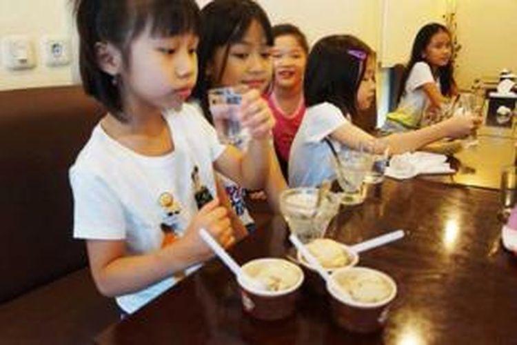 Anak-anak menikmati es krim aneka rasa.