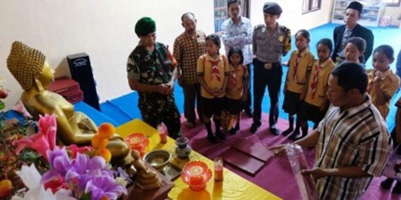 Anggota Bhabinkamtibmas dan Babinsa bersama rombongan mendengarkan penjelasan tokoh agama Buddha di vihara saat berkeliling mengunjungi tempat ibadah di kampung toleransi di Temanggung.