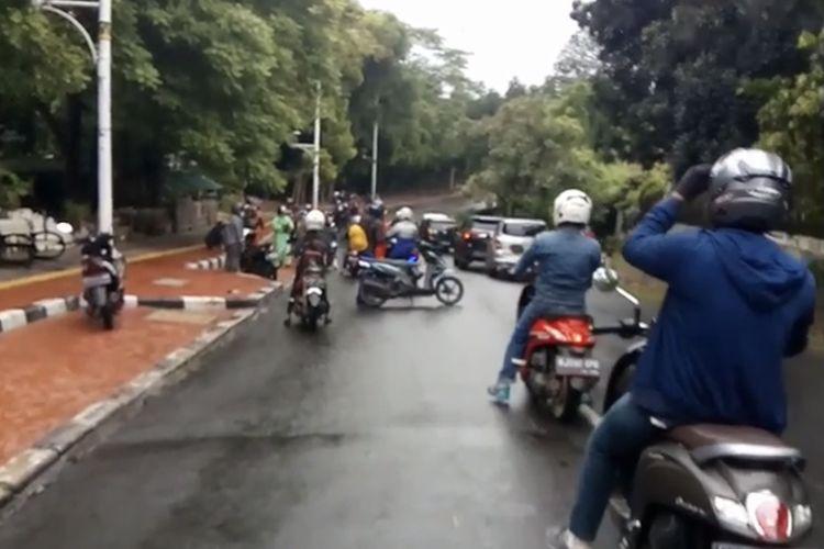 Pemotor yang jatuh saat melewati jalan penuh oli bercampur air hujan