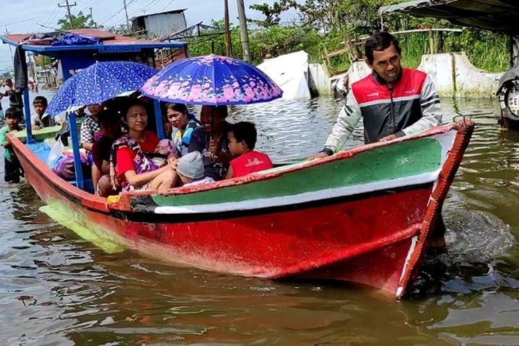 Warga menaiki perahu untuk menerobos banjir di Jalan Kusuma Bangsa Kota Pekalongan Jawa Tengah.