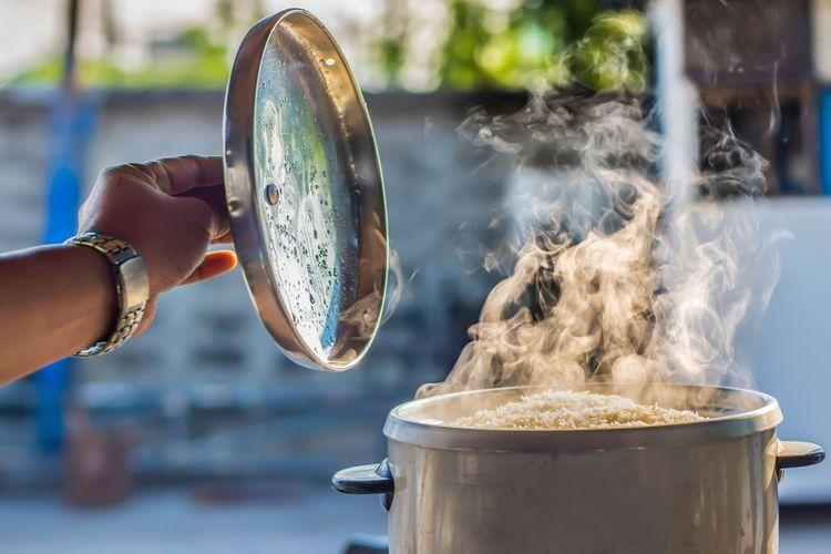 Ilustrasi orang sedang menanak nasi.