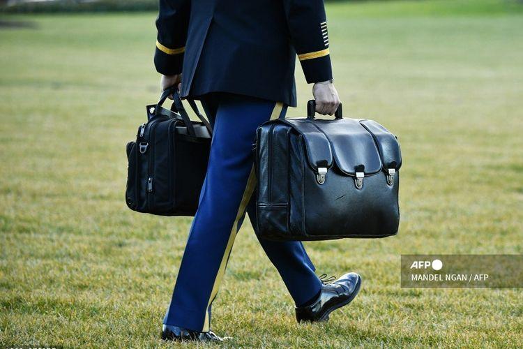 Seorang asisten militer membawa bola nuklir dengan peralatan dan kode nuklir, saat Presiden AS Donald Trump dan First Lady Melania terbang dengan Marine One menuju Florida.